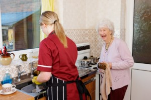 carer helps her elderly patient by washing the dishes for her