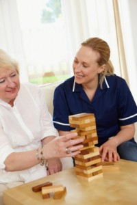 Home Care Nurse playing Jenga game with elderly woman in her home