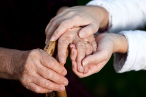 close up of nurse holding elderly person's hand