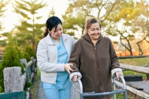 asain nurse helping latino woman walk with walker